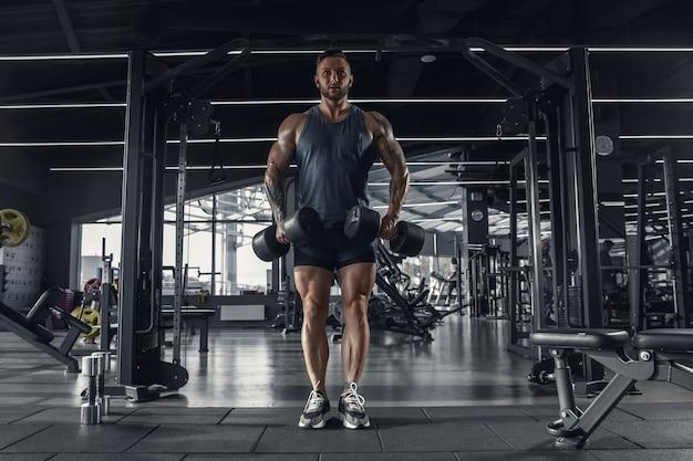 Joven atleta caucásico muscular practicando en el gimnasio con las pesas.
