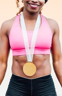 Joven atleta celebrando la victoria con medalla de oro alrededor de su cuello