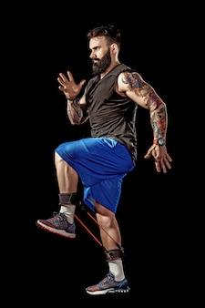 Joven atleta ejercicio en cuclillas con banda de resistencia alrededor de las piernas. longitud total del cuerpo sobre fondo negro de estudio.