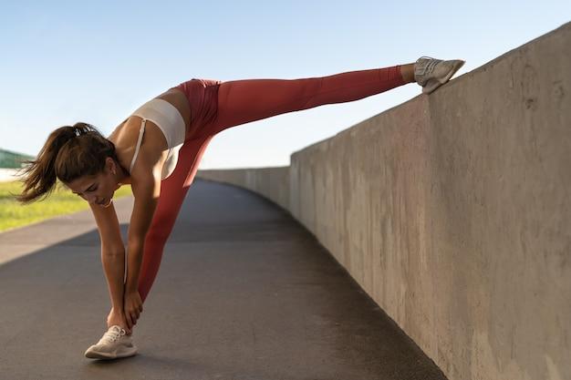 Joven atleta se extiende y calienta al aire libre