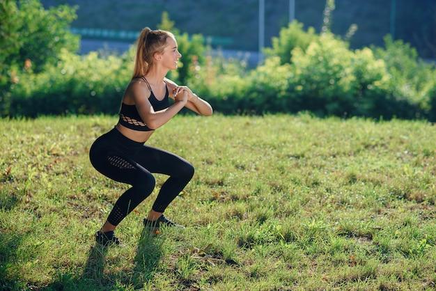 Joven atleta femenina haciendo ejercicios de sentadillas al aire libre en el parque. chica en forma trabajando su núcleo y glúteos con peso corporal.