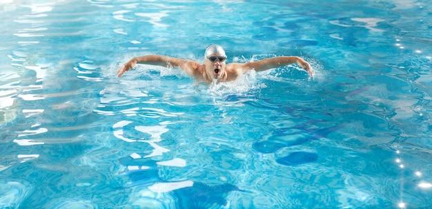 Joven atleta guapo nadando en encuesta en estilo mariposa