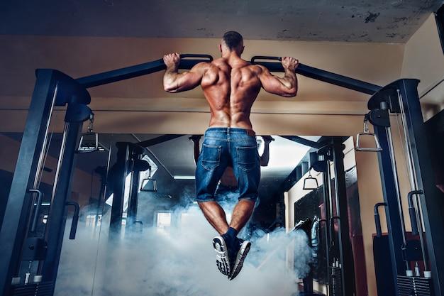 Joven atleta haciendo ejercicio en barras en gimnasio