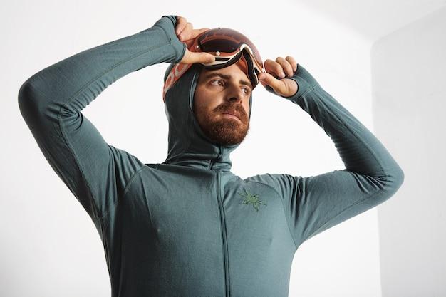Joven atleta masculino barbudo equipado en suite térmica de capa base con las manos en sus gafas de snowboard, mirando de lado, aislado en blanco