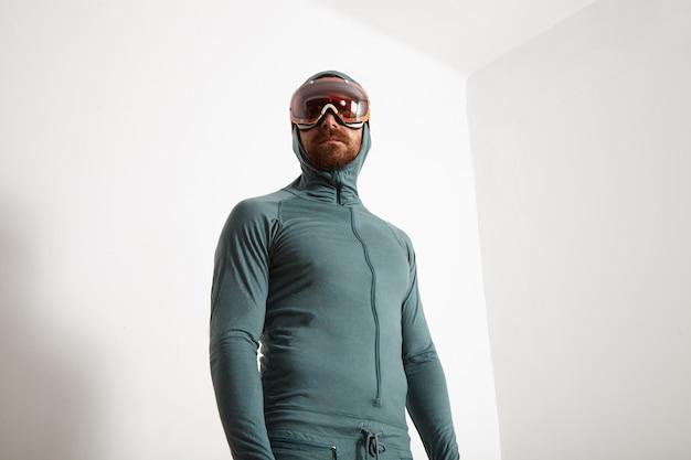 Joven atleta masculino barbudo equipado en la suite térmica de capa base usa gafas de snowboard, mirando de lado, aislado en la pared blanca