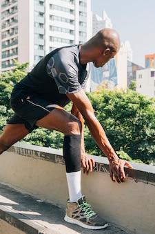 Joven atleta masculino entrenando y haciendo ejercicios al aire libre en la ciudad