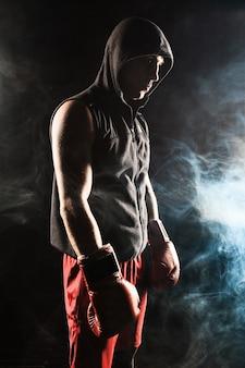 El joven atleta masculino kickboxing de pie sobre un fondo de humo azul
