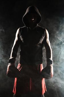 Joven atleta masculino kickboxing de pie sobre un fondo de humo azul
