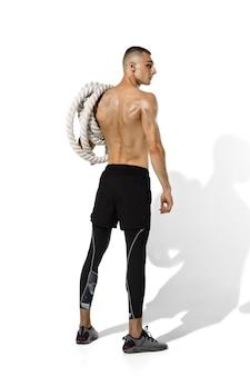 Joven atleta masculino posando en blanco con sombras