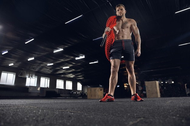 Joven atleta masculino sano haciendo ejercicios en el gimnasio