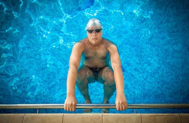 Joven atleta masculino sosteniendo en el borde de la piscina y preparándose para nadar