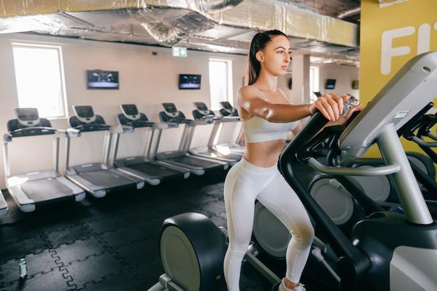 Joven atleta mujer cardio entrenamiento en gimnasio.