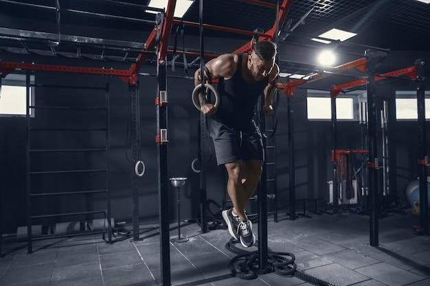 Joven atleta muscular practicando dominadas en el gimnasio con los anillos