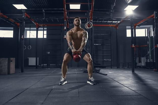 Joven atleta muscular practicando sentadillas en el gimnasio con el peso