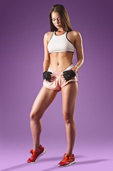 Joven atleta musculoso posando en espacio lila