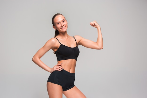 Joven atleta musculoso posando en gris