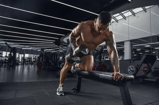 Joven atleta musculoso practicando en el gimnasio con las pesas