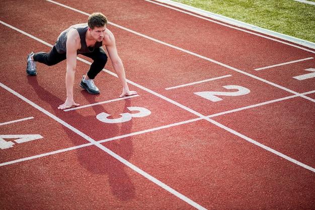 Joven atleta en posición inicial listo para comenzar una carrera