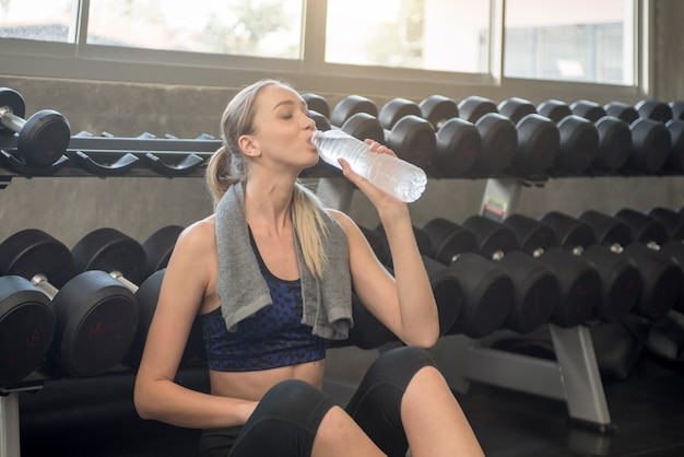 Joven atlética agua potable en un gimnasio.