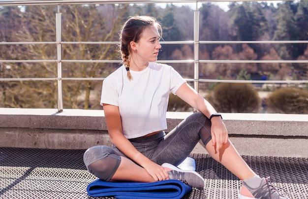 Joven atlética con una camiseta blanca y leggings grises se sienta en una alfombra de gimnasia al aire libre en un clima soleado en la terraza. foto horizontal