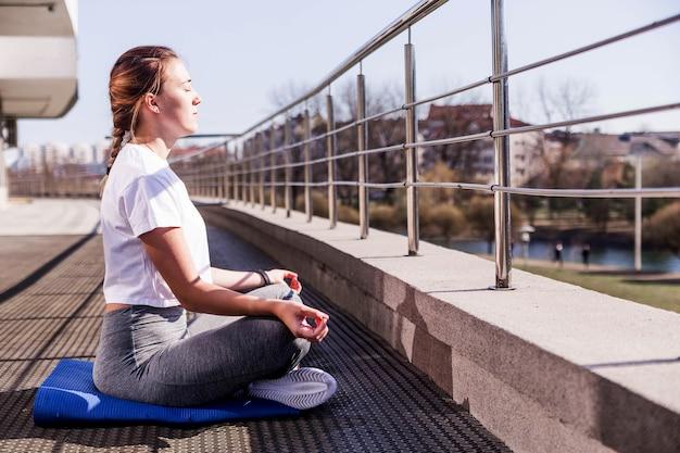 Joven atlética con una camiseta blanca y mallas grises se sienta en posición de loto al aire libre en un clima soleado en la terraza. foto horizontal