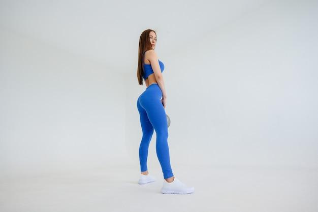 Una joven atlética se encuentra con un estudio sobre un fondo blanco.