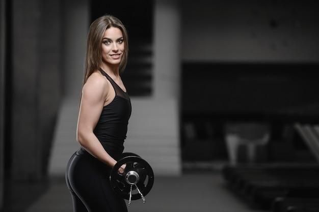 Joven atlética fuerte trabajando en el gimnasio