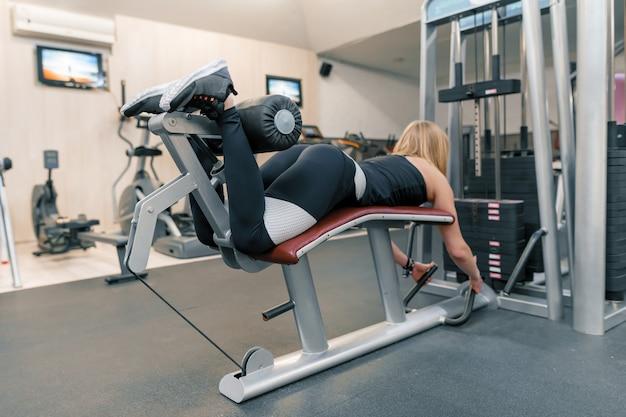 Joven atlética haciendo ejercicios en las piernas y las nalgas en el gimnasio