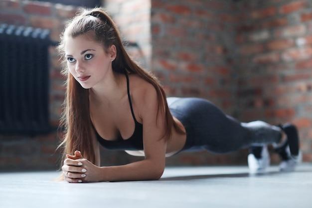 Joven atlética haciendo su rutina de ejercicios en casa