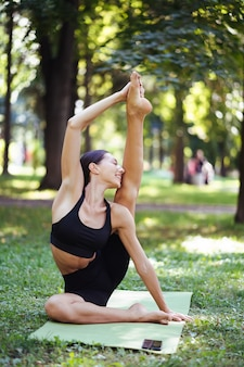 Joven atlética haciendo yoga en el parque por la mañana, entrenamiento de mujeres en una estera de yoga