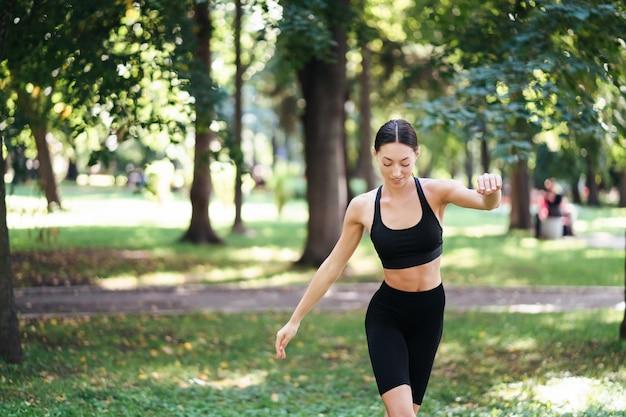 Joven atlética haciendo yoga en el parque por la mañana