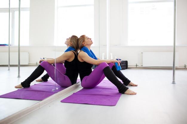 Joven atlética mujer rubia descansando después de hacer ejercicio en el gimnasio cerca del espejo
