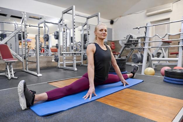 Joven atlética muscular haciendo ejercicios de estiramiento en el gimnasio