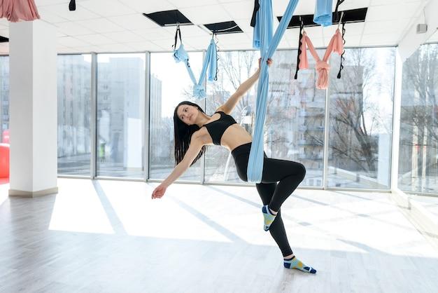 Joven atlética practica yoga relax, estiramiento en un ejercicio usando una hamaca después de un duro día de trabajo.