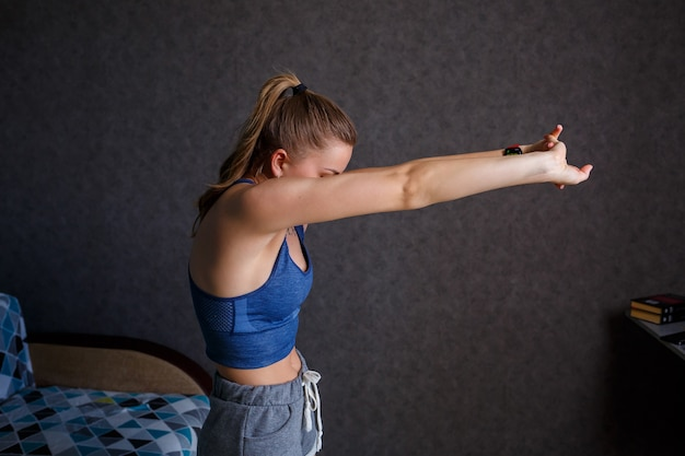 Joven atlética practicando yoga, estiramiento corporal, ejercicio, entrenamiento, vistiendo ropa deportiva, camiseta azul, pantalones cortos, cerca del sofá en casa