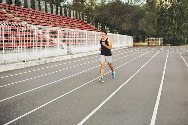 Joven atlético corriendo en el estadio en la mañana
