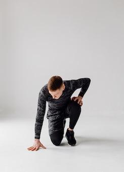Joven atlético haciendo entrenamientos en casa, hombre haciendo entrenamiento, calentamiento antes del ejercicio con pesas.