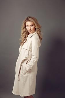 Joven atractiva con abrigo beige