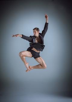 La joven y atractiva bailarina de ballet moderno saltando sobre fondo gris