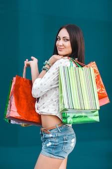 Joven atractiva con bolsas de compras al aire libre