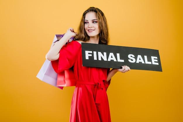 Joven atractiva con cartel de venta final y coloridos bolsos de compras aislados sobre amarillo