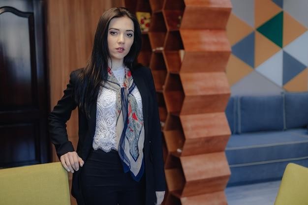 Joven atractiva chica emocional en un estilo de negocios en una silla en una oficina moderna o audiencia