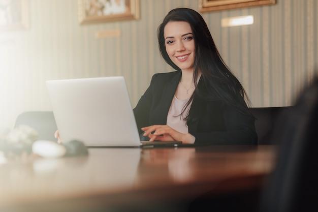 Joven atractiva chica emocional en ropa de estilo empresarial sentado en un escritorio en una computadora portátil y teléfono en la oficina o auditorio