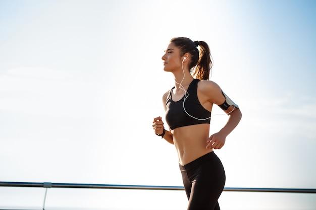 Joven atractiva chica de fitness para correr