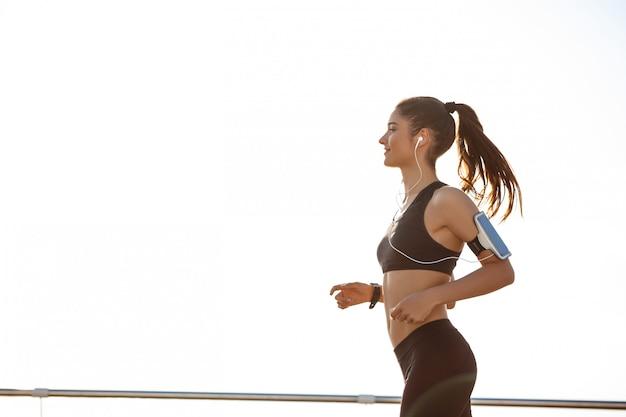 Joven y atractiva chica de fitness trotar junto al mar