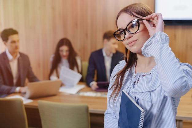 Joven y atractiva chica oficinista con estilo en gafas con un cuaderno en la mano