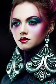 Joven atractiva chica rubia en maquillaje de arte brillante, cabello alto, pintura corporal. diamantes de imitación y brillo