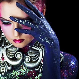 Joven atractiva chica rubia en maquillaje de arte brillante, cabello alto, pintura corporal. palma en la cara