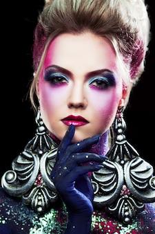 Joven atractiva chica rubia en maquillaje artístico brillante, tocando los labios
