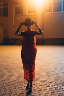 La joven y atractiva chica con sombrero posa ante la cámara por la noche.